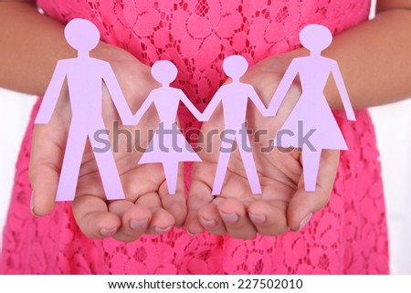 Woman hands holding paper family close up - stock photo