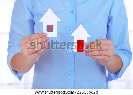 Woman hands holding paper houses on light background