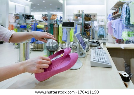 Woman hands holding price scanner. Fashion clothing store. Cashier register,  computer on sales counter in shop. Shoes, pricing, shopping. - stock photo