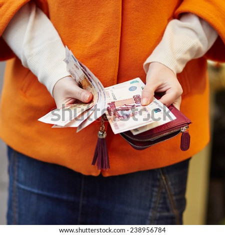 Woman hands holding purse with Russian roubles, financial crisis in Russia concept - stock photo