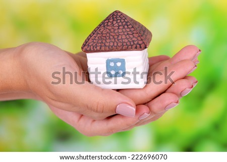 Woman hands holding small house on bright background - stock photo