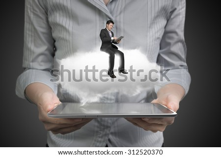 Woman hands holding smart tablet with businessman sitting on white cloud, on dark gray background. - stock photo