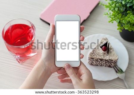 woman hands holding white phone with isolated screen on a table in a cafe - stock photo