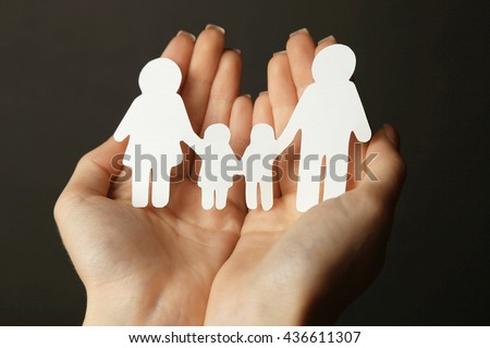 Woman hands holding wooden family shape. Love and relationships concept