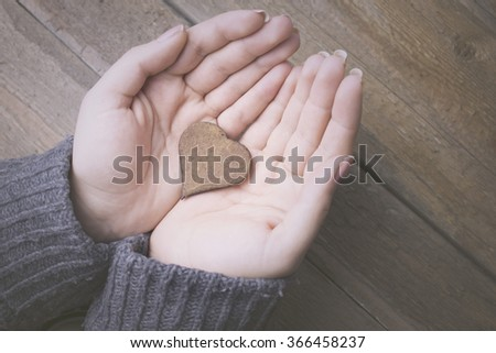 woman hands holding wooden heart