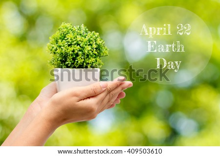 Woman hands in jardiniere on a natural background and text  April 22 Earth Day .Concept Earth Day - stock photo