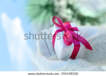 Woman hands in knitted mittens holding gift on winter background