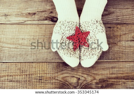 Woman hands in light teal knitted mittens are holding red snowflake on wooden background. Winter and Christmas concept. - stock photo