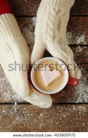 Woman hands in mittens holding a cup of coffee