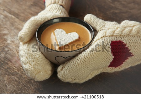 Woman hands in mittens holding a cup of coffee - stock photo