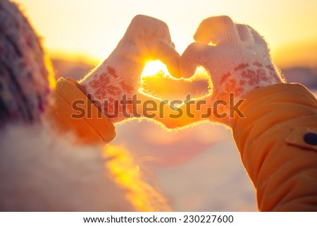 Woman hands in winter gloves Heart symbol shaped Lifestyle and Feelings concept with sunset light nature on background - stock photo