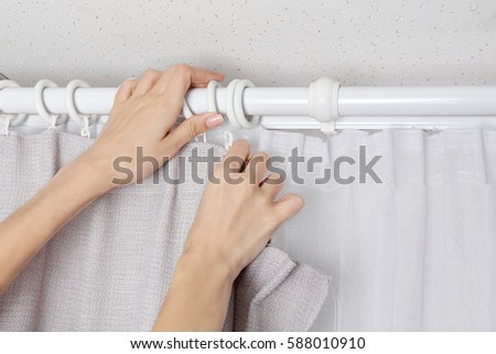 Woman Hands Installing Curtains Over Window
