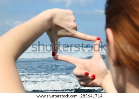 Woman hands making a frame against the blue ocean blur  - stock photo