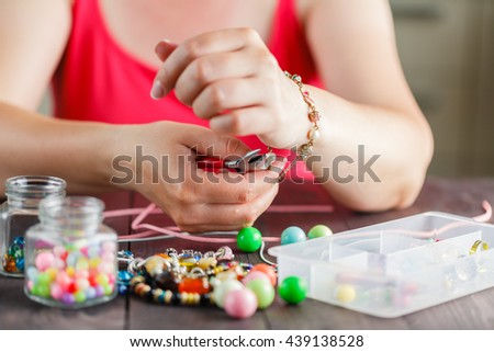 Woman hands making bracelete with plastic beads