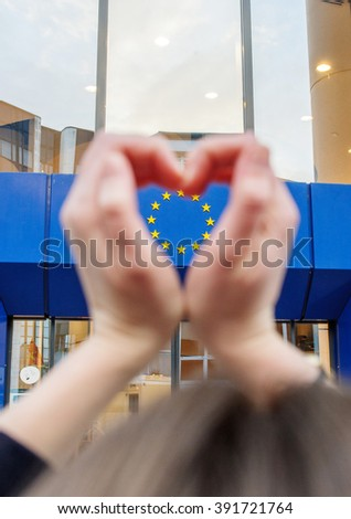 Woman hands making shape of love heart with the stars of European Union in the l hearts shape - stock photo