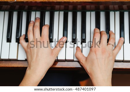 woman hands on a piano key. Playing music. selective focus technique