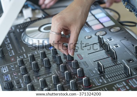 Woman hands on DJ equipment deck and mixer - stock photo