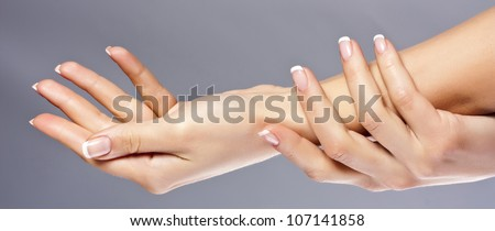 Woman hands on grey background, isolated - stock photo