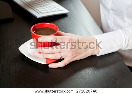 Woman hands on red cup of coffee on an office table - stock photo
