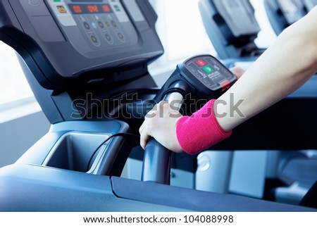 Woman hands on the running machine in fitness club - stock photo