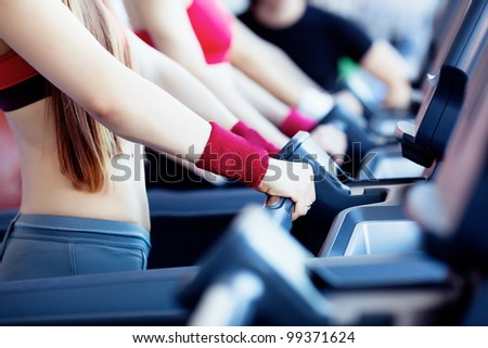 Woman hands on tracking machine in fitness center - stock photo