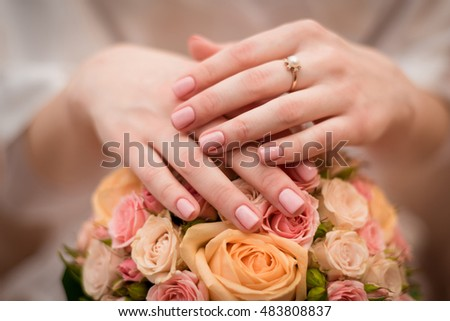 woman hands on wedding bouquet with engegment ring