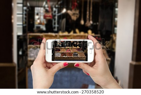 Woman hands photo online with a smart phone. Travel photo storefront. - stock photo