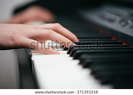 Woman hands playing piano - stock photo
