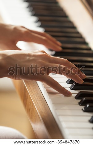 woman hands playing piano, selective focus