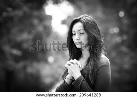 Woman hands praying on Outdoors black and white - stock photo