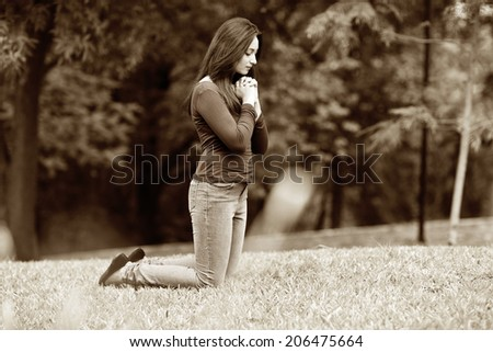 Woman hands praying Outdoors black and white - stock photo
