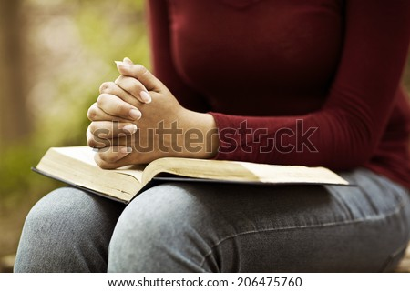 Woman hands praying with a bible in his legs Outdoors - stock photo