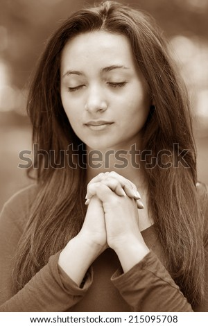 Woman hands praying with a blible in his legs Outdoors, sepia black and white - stock photo