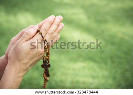 Woman hands praying with a rosary - stock photo