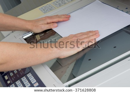 woman hands putting a sheet of paper into a copying device - stock photo