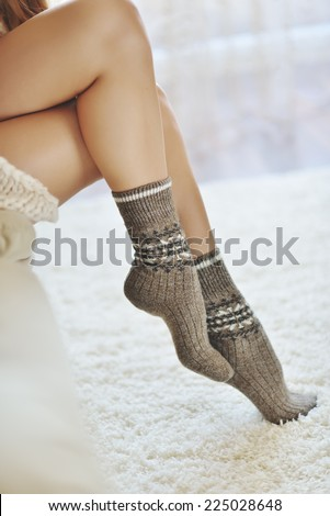 Woman hands putting on warm woolen socks.  - stock photo