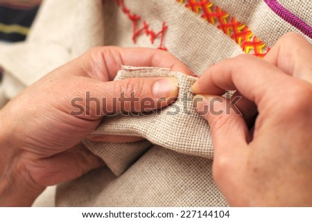 Woman hands sewing with needle and thread close-up