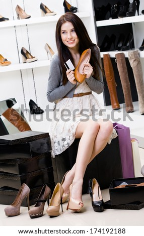 Woman hands shoes and credit card in the footwear shop where she would like to buy new pumps - stock photo