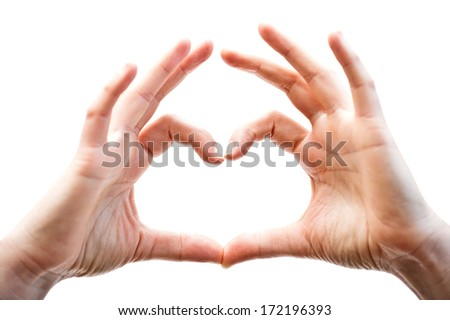 Woman hands showing heart gesture, isolated on the white background, with light coming from inside the shape