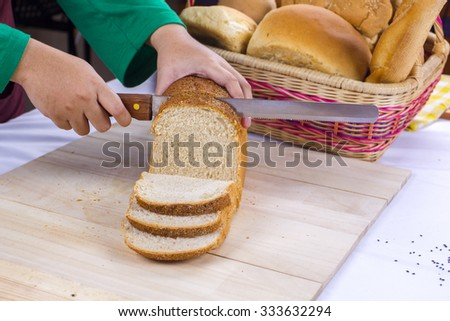 woman hands slicing home made bread - stock photo