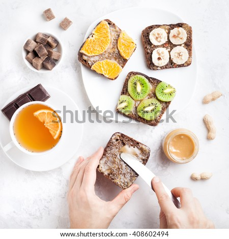 Woman hands spreading peanut butter on the bread in the morning on white marble background   - stock photo