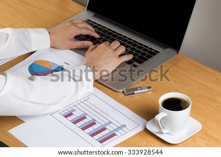 Woman hands typing on laptop keyboard with printed graphs, coffee, and thumb drive on desktop. - stock photo