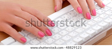 Woman hands typing on the white keyboard