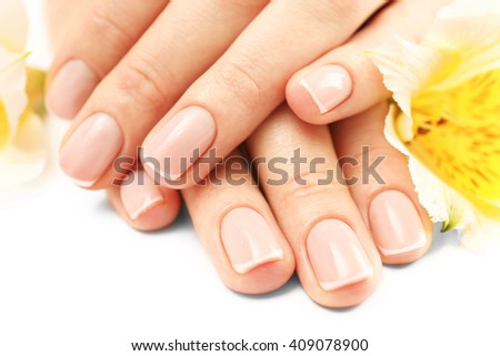 Woman hands with beautiful manicure and white lily on white background, close up - stock photo