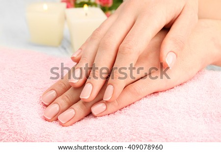 Woman hands with beautiful manicure on pink towel - stock photo