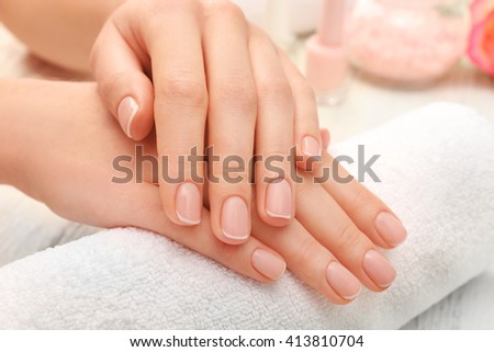 Woman hands with beautiful manicure on towel, close up - stock photo