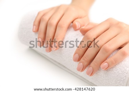 Woman hands with beautiful manicure on white towel - stock photo