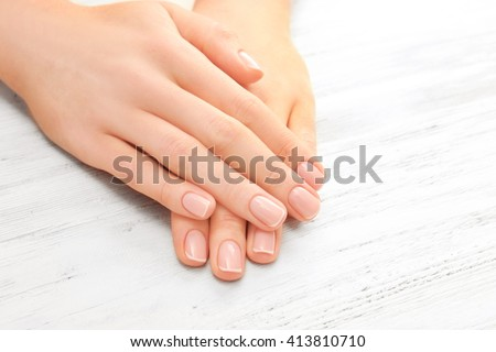 Woman hands with beautiful manicure on wooden background - stock photo