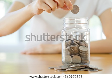 Woman hands with coins in glass jar, close up