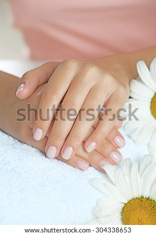 Woman hands with french manicure and chamomile on towel close-up